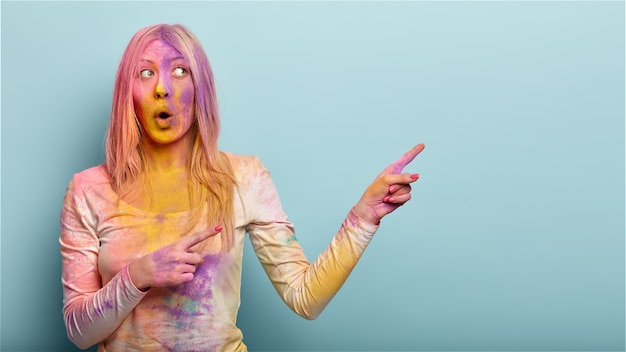 Confused shocked woman asks what happened, points away on free space for advertisement, covered with holi powder