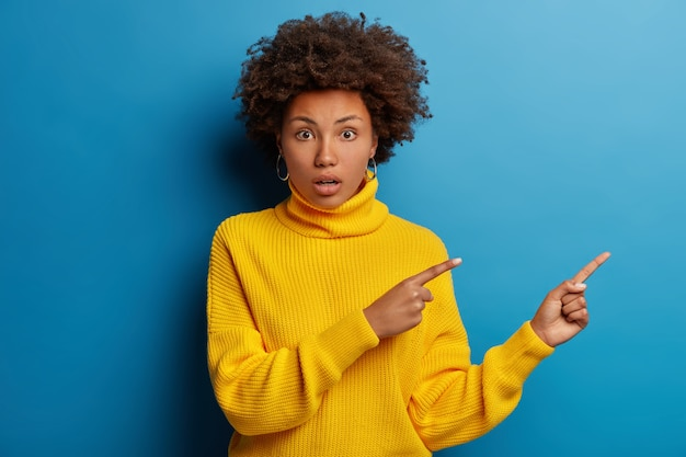 Confused shocked woman with afro haircut points aside, realizes something amazing happened, has worried anxious expression isolated on blue background