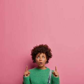 Confused shocked woman with afro hairstyle, points upwards