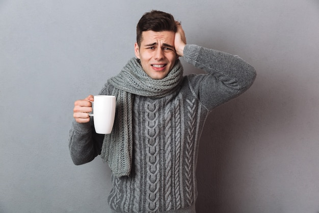 Confused sick man в свитере и шарфе с головной болью, держа чашку чая и глядя