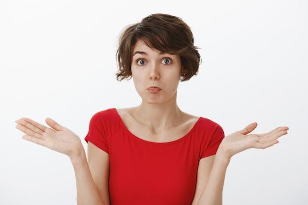 Donna sciocca confusa che scrolla le spalle, essendo inconsapevole, non ne ha idea