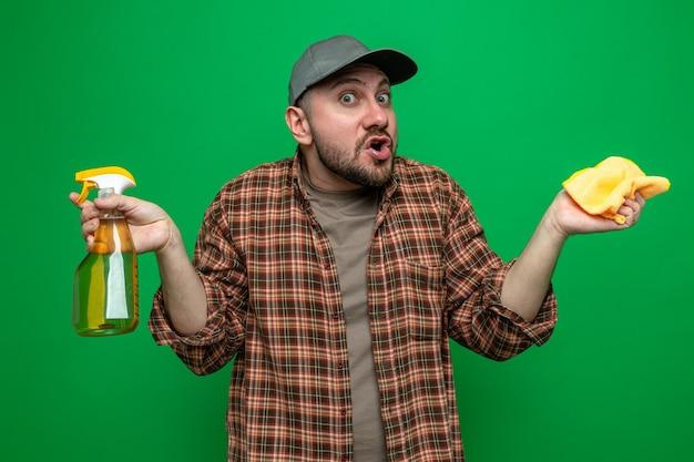 Uomo delle pulizie slavo confuso che tiene in mano panni per la pulizia e detergente spray
