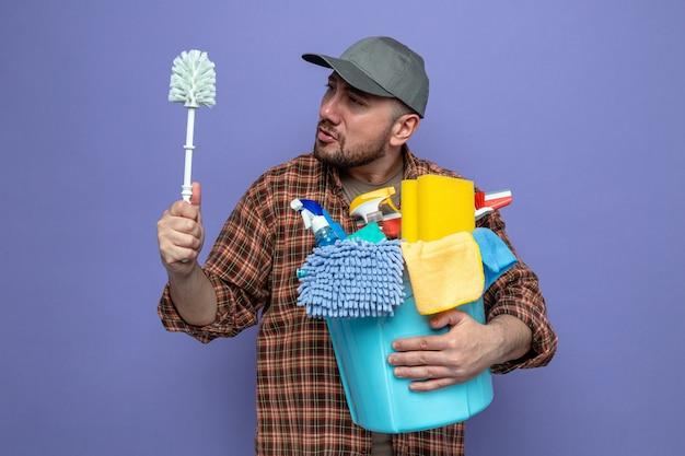 Uomo delle pulizie slavo confuso che tiene in mano l'attrezzatura per la pulizia e guarda lo scopino del wc