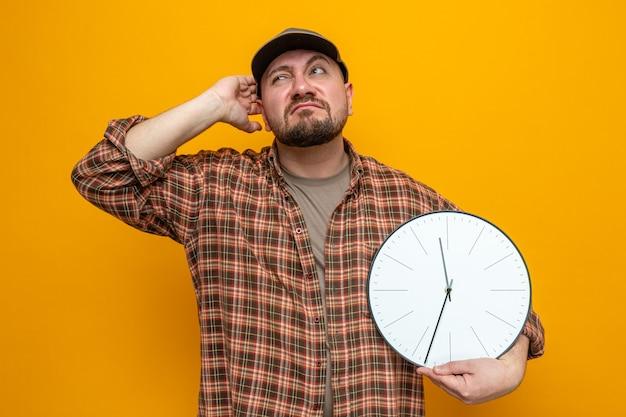 Uomo delle pulizie slavo confuso che tiene l'orologio e si gratta la testa guardando di lato Foto Gratuite