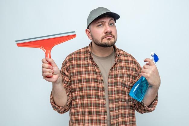 Смущенный славянский уборщик, держащий ракель и спрей-очиститель