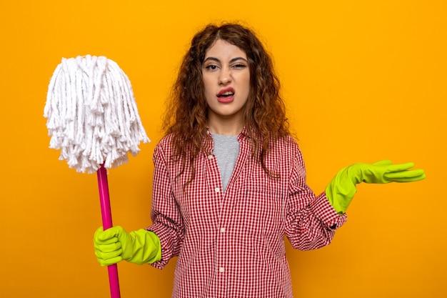 Confusa mano di diffusione giovane donna delle pulizie che indossa guanti che tengono mop isolato su parete arancione