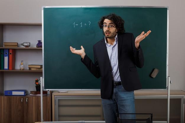 Mani allargate confuse giovane insegnante maschio con gli occhiali in piedi davanti alla lavagna in aula