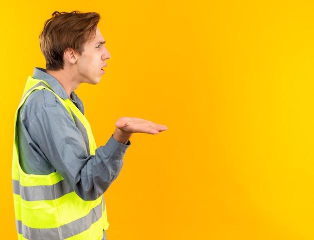 프로필 보기에 혼란스러운 서 있는 젊은 빌더 남자는 복사 공간이 있는 노란색 벽에 격리된 제복을 입은 손을 펴고 있습니다.