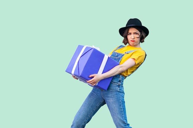세련된 힙스터를 입은 강한 소녀는 데님 작업복을 입고 검은 모자를 쓰고 서 있고 연약한 얼굴을 가진 거대하고 무거운 선물 상자를 잡으려고 합니다. 스튜디오 촬영, 녹색 배경, 절연