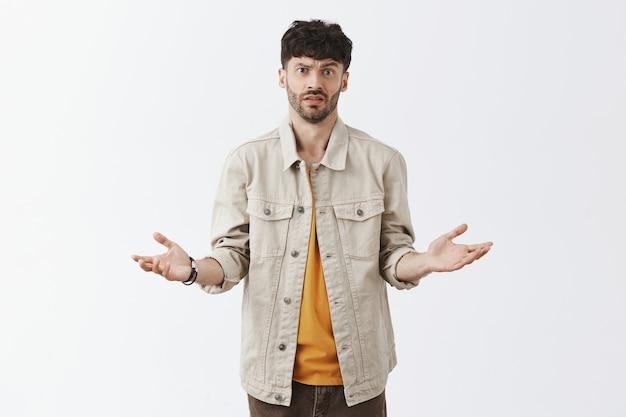 Смущенный стильный бородатый парень позирует у белой стены