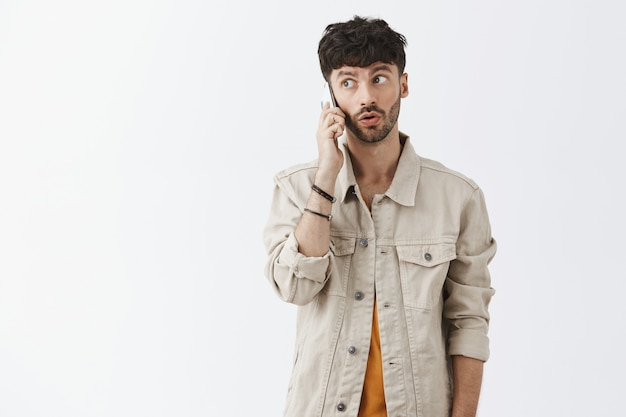Confused stylish bearded guy posing against the white wall