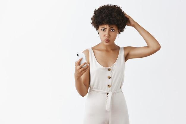 Ragazza alla moda confusa che posa contro il muro bianco