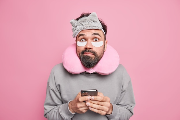 Confused surprised man with beard uses neck pillow for better sleep applies beauty patches under eyes holds smartphone poses indoor against pink wall avoids stiffness going to have nap