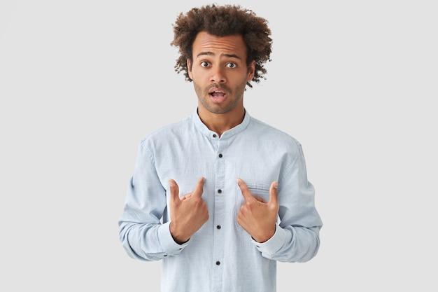 Il giovane maschio afroamericano sorpreso e confuso indica se stesso con stupore, ha uno sguardo perplesso, vestito con una camicia alla moda, si chiede di essere scelto, sta da solo contro il muro bianco