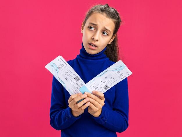 コピースペースでピンクの壁に隔離された側を見て飛行機のチケットを保持している混乱した10代の少女