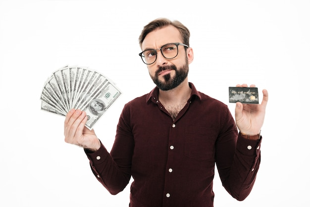 Confused thinking young man holding money and credit card.