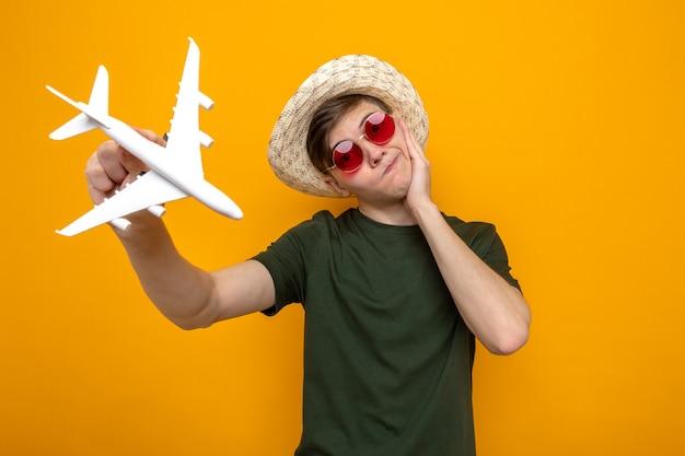 Смущенный, наклонив голову, положив руку на щеку, молодой красивый парень в шляпе с очками держит игрушечный самолетик