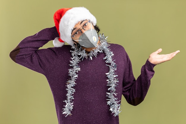 クリスマスの帽子と首に花輪と手を広げてオリーブグリーンの背景で隔離の頭の後ろに手を置く医療マスクを身に着けている混乱した傾斜頭の若いハンサムな男