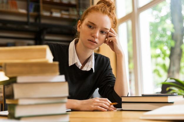 Смущенный усталый рыжий студент сидит за столом с книгами в библиотеке и пишет заметки