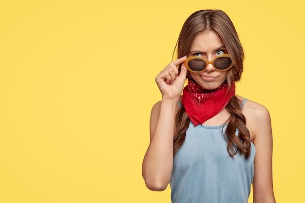 혼란스러워하는 불확실한 백인 여성이 선글라스에 손을 대고, 눈썹을 올리고, 빨간 두건을 입고, 약간 빗질 한 땋은 머리를하고, 우울한 표정으로 위쪽으로 보이는, 노란색 벽 위에 절연