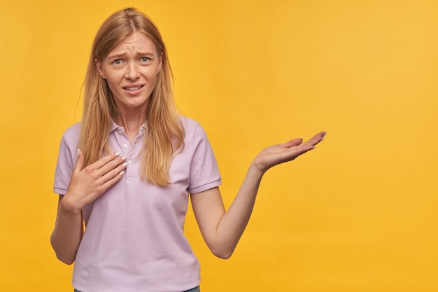 Confused unhappy blonde young woman with freckles in lavender tshirt pointing at herself by hand and holding empty space on palm over yellow wall