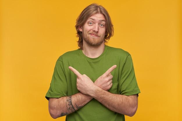 금발 헤어 스타일을 가진 혼란스럽고 확실하지 않은 수염 난 남자. 녹색 티셔츠를 입고. 문신이 있습니다. 그의 얼굴을 비틀어 라. 복사 공간에서 양쪽을 가리키는 노란색 벽 위에 절연