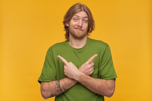 Confused, unsure bearded guy with blond hairstyle. wearing green t-shirt. has tattoo. wry his face.  and pointing both sides at copy space, isolated over yellow wall