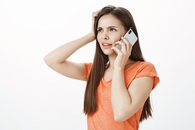 Ragazza confusa e insicura che guarda nell'angolo in alto a sinistra perplessa mentre parla al telefono cellulare