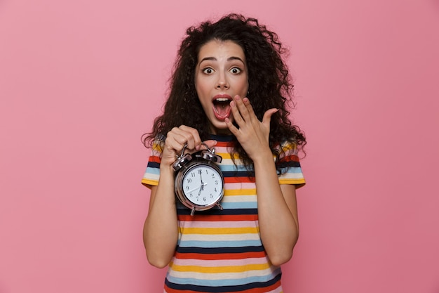 ピンクで隔離の目覚まし時計を保持している巻き毛の20代の混乱した女性