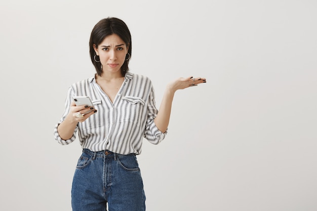 Confused woman asking what while using mobile phone, shrugging puzzled