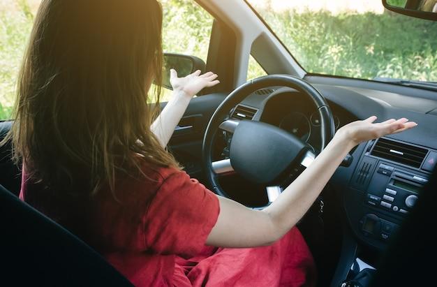 ハンドルの後ろの混乱した女性。運転中の不明な状況。