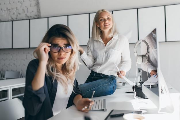 彼女の金髪の同僚がオフィスのテーブルに座っている間、眼鏡を保持している黒いジャケットの混乱した女性。忙しい仕事中にポーズをとる悲しい秘書の屋内肖像画。