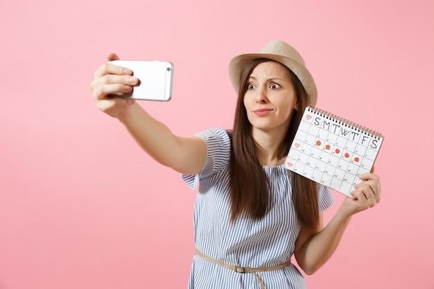 Смущенная женщина в синем платье делает селфи на мобильном телефоне, держа календарь периодов для проверки дней менструации, изолированных на розовом фоне. медицина, здравоохранение, гинекологическая концепция. скопируйте пространство.