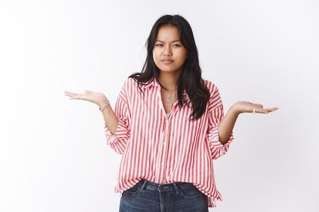 Смущенная женщина, стоящая на вопросе в невежественной позе, пожимает плечами и поднимает руки в неуверенном и неосознанном жесте, хмурясь, прищурившись в камеру, обеспокоенная, не может понять через белую стену