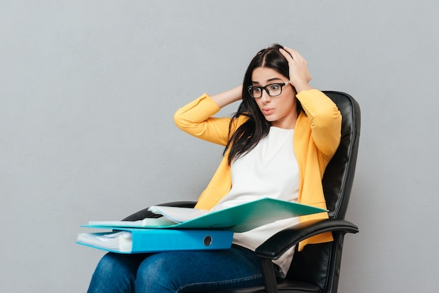 Confused woman wearing eyeglasses and dressed in yellow jacket holding folders while sitting on office chair and looking at folders over grey surface.
