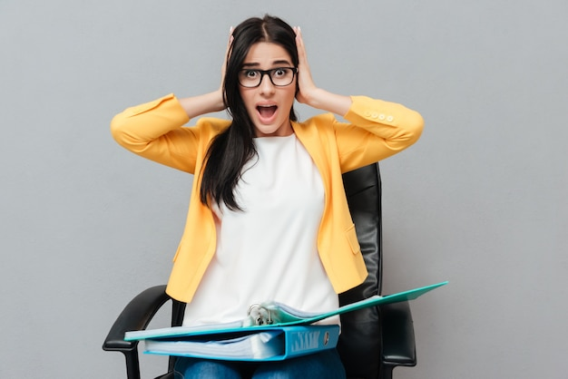 Confused woman wearing eyeglasses holding folders while sitting on office chair and looking at front over grey surface.
