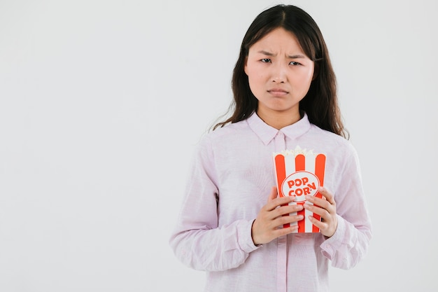Confused woman with a bag of popcorn