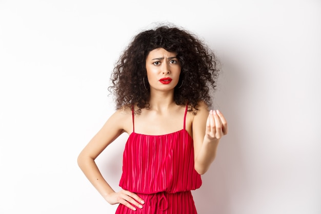 곱슬 머리를 가진 혼란스러운 여자, 빨간 드레스를 입고, 인상을 찌푸리고 손을 떨고, 흰색 배경에 서서 주저하고, 뭔가를 이해할 수 없습니다.