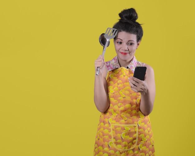 Смущенная женщина со смартфоном в одной руке и посудой в другой