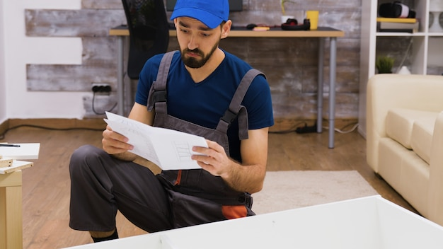 Confused worker in overalls reading instructions for furniture assembly wearing a cap.