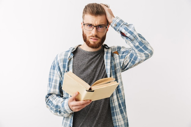 Confused worried bearded man in shirt and eyeglasses holding book