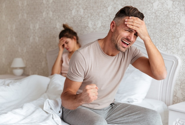 Confused worried man sitting on bed with his girlfriend