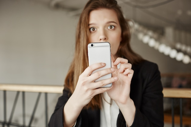 Confused worried woman looking at you while using mobile phone