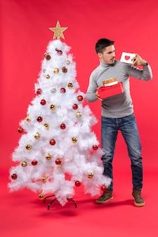 装飾されたxsmasの木の近くに立って、赤で彼の贈り物を保持している灰色のブラウスで混乱した若い大人