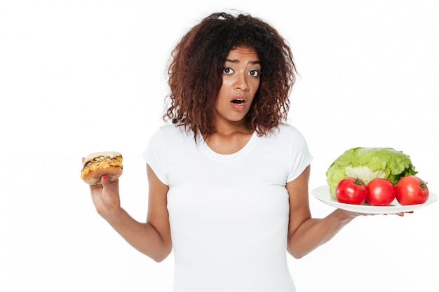 Confused young african woman choosing between burger and vegetables.