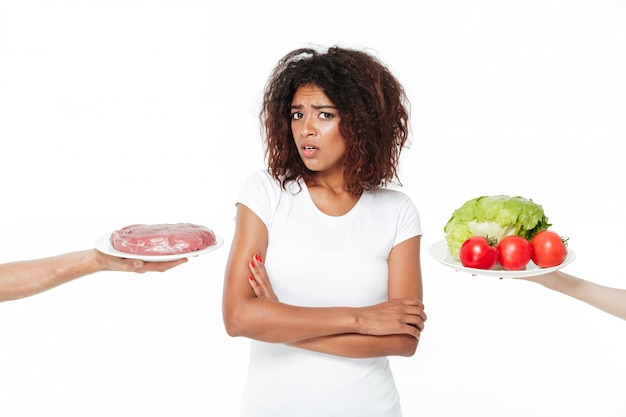 Confused young african woman choosing between meat and vegetables.