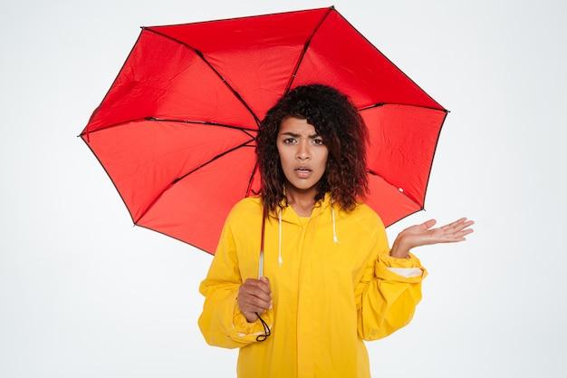 傘の下に隠れているレインコートで混乱している若いアフリカ人女性