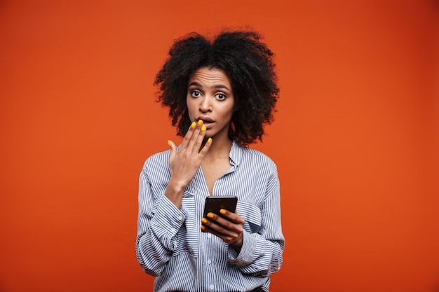 Confused young african woman using mobile phone isolated over red wall