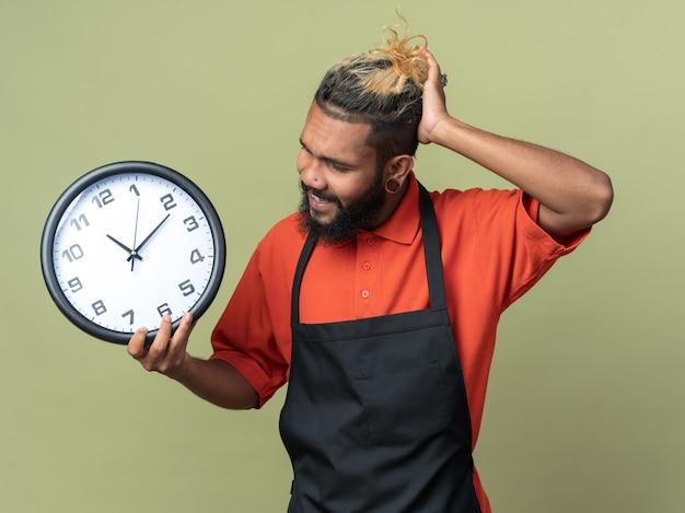Giovane barbiere afroamericano confuso che indossa l'uniforme che tiene e guarda l'orologio che tiene la mano sulla testa