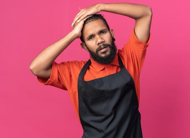 Giovane barbiere maschio afroamericano confuso che indossa l'uniforme che tiene le mani sulla testa